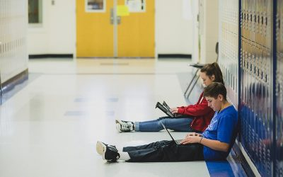 Two students lean against lockers while working off of laptops