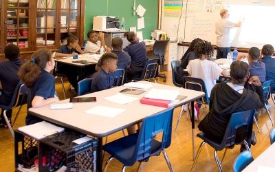 Teacher stands in front of white board inside classroom while students in seats look on