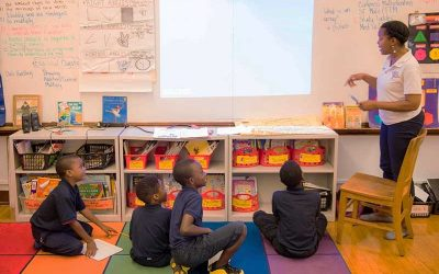 Four students sit on colorful floor, looking up at teacher as she gestures at white board