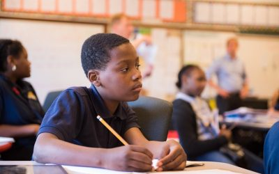 Student sits in classroom, looking off to the side as he holds a pencil