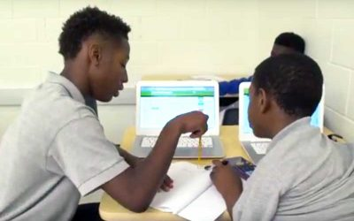 Photo of two students working together with notebooks and laptop computers