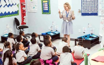 Photo of teacher standing in front of class teaching to group of seated students