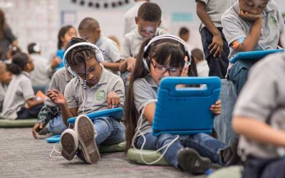 Photo of multiple students seated at desks and on floor using devices with headphones