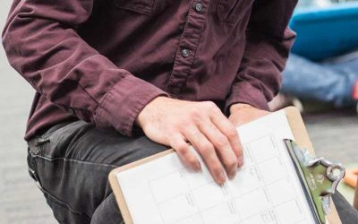 Photo closeup of clipboard containing paper schedule with teacher in background