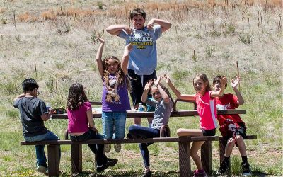 Students sit, smiling, at outdoor picnic table with arms raised in the air