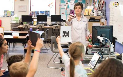 Teacher holds up smartphone in front of students as they raise pieces of paper