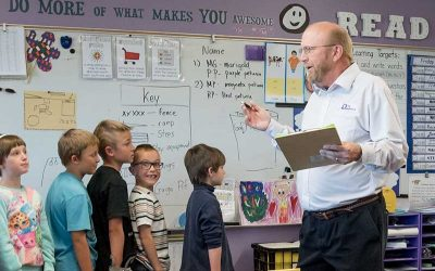 Students stand in line in front of teacher while he holds notebook, speaking
