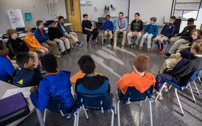 Male students and teacher seated in a circle formation