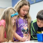 Three elementary students working together at table with several resources
