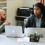 Teacher speaks to student as she looks at laptop