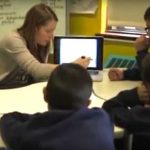 Photo of teacher explaining content from laptop to a group of students
