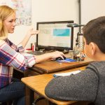 Teacher gestures at computer screen while meeting with student