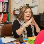 Teacher sits at desk, gesturing as she speaks