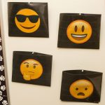 Four folders placed on a wall, each with a different emoji face