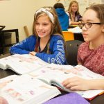 Students smile, talk with books in front of them