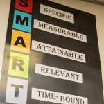 Photo of poster board that reads SMART: Specific, Measurable, Attainable, Relevant, Time-Bound