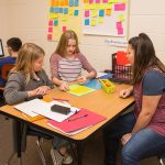 Teacher works with pair of students at small desk