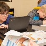 Student looks closely at laptop while other students work around him