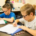 Two students fill out worksheets