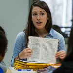 Teacher holds open book, presenting it to students, talking