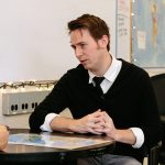 Teacher sits at desk, looking forward and talking to someone