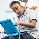 Elementary student looks closely at tablet, wears headphones