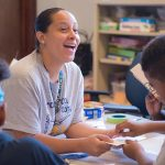 Teacher smiles, laughs while sitting at table with students