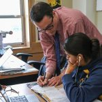 Teacher leans down next to student desk, writing on paper as student looks on