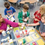 Teacher and four students look over project that shows a small 3-D model of a city