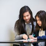Two students working together at desk, looking on together at paper