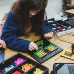 Student works on project, placing colorful blocks in a small grid
