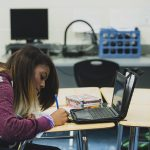 Student writes on paper at desk, sitting in front of laptop