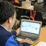 Photo of student and his laptop with screen showing data dashboard