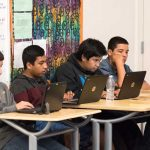 Photo of group of students working on laptops at classroom table