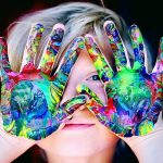 A child's raised hands with bright, multicolored swirls of paint on both palms with the child's eyes peeking through their spread fingers.