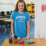Student smiles for photo, standing in front of table with experiment materials
