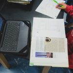 Overhead view of student studying from book, in front of laptop