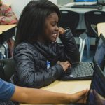 Student smiles as she looks at laptop