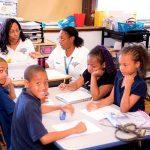 Four students sit at grouped desks alongside two educators inside classroom
