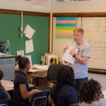 Teacher stands in front of classroom, pointing to paper in his hand as students look on