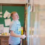Teacher looks up at white board in front of classroom