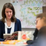 Teacher reads book inside classroom