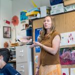 Teacher gestures as she speaks to room