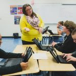 Teacher speaks with student while he sits at joined desks with other students who are looking at their laptops