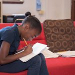 Student sits on red couch, leaning forward as she writes on paper