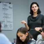 Teacher stands up inside classroom, gesturing
