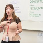 """Teacher stands and gestures to class in front of white board, in the background the word """"Success"""" is visible"""