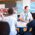Educator works with four students at a table in a semi-circle shape