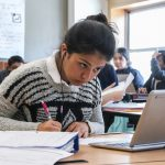 Student leans down, looking over paper with pen and hand as she looks at laptop in front of her on a desk