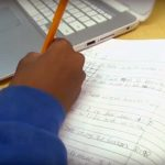 Photo closeup of student working in workbook with device closeby